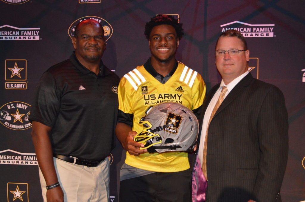 Shawn Robinson holds the Army All-American helmet with Anthony Williams, Texas Dir. Of Player Development /Scouting for the All-American Games and DeSoto Eagles Head Coach Todd Peterman. (Submitted Photo/DeSoto ISD Media Relations)