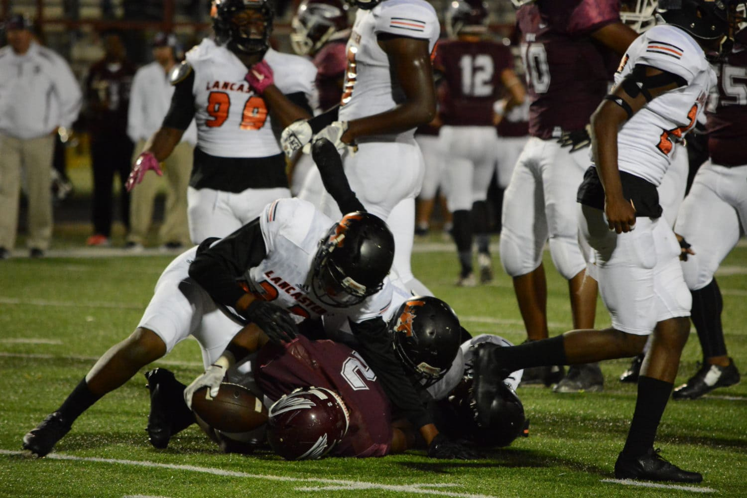 Lancaster High School linebacker Sir Charles Miles-Frost (32) tackles Red Oak running back Blake Sonnier (2) in the 1st half of the Tigers' game against the Hawks at Red Oak's Billy Goodloe Stadium. The Lancaster Tigers beat the Hawks 46-7 at Red Oak's Billy Goodloe Stadium. (Photo by Joshua Bustamante/Tiger Student Media)