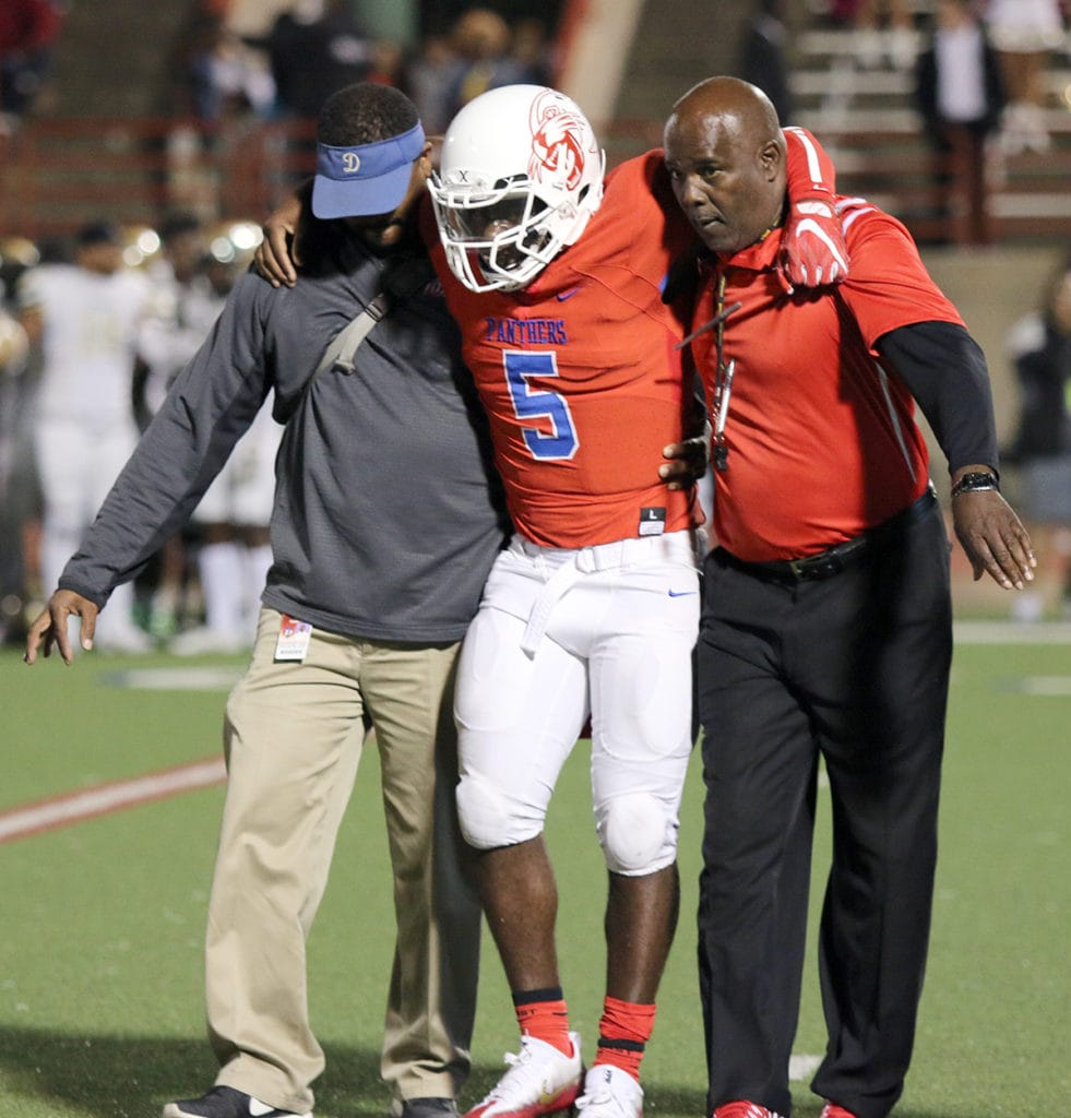 Duncanville Quarterback Jaylin Nelson is supported by an athletic trainer and Coach Reginald Samples as he makes his way off the field Friday, October 21, 2016. Nelson suffered a broken femur bone during the first quarter of the Suburban Bowl versus DeSoto. (Jose Sanchez/Duncanville High School)