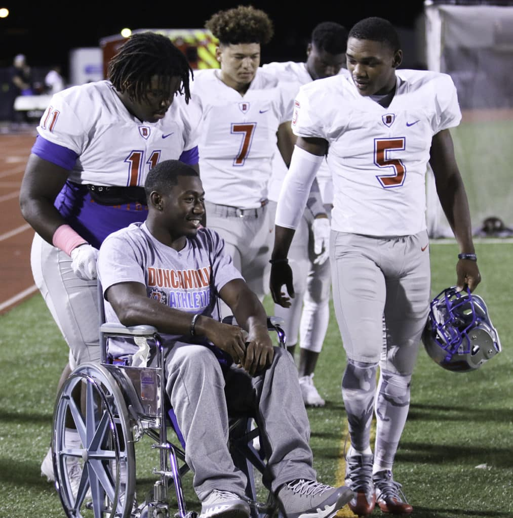 Panthers' captains wheel injured quarterback Jaylin Nelson onto the field for the first time since his season ending injury last week. Jaylin watched the game from the sidelines and rooted for his backup quarterback and teammates. (Jose Sanchez/Duncanville High School)