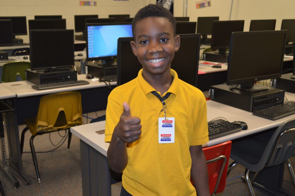West Middle School student receives 'I Voted' sticker after casting online ballot.