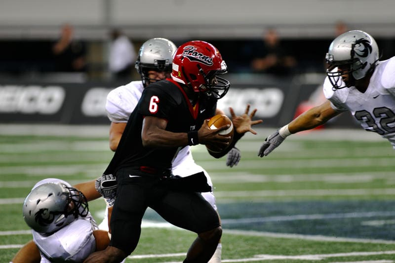 2010 Cedar Hill Quarterback Driphus Jackson (Rice University) battles to gain yardage against the Denton Guyer defense during the Longhorns and Wildcats last playoff meeting in 2010. (File Photo)