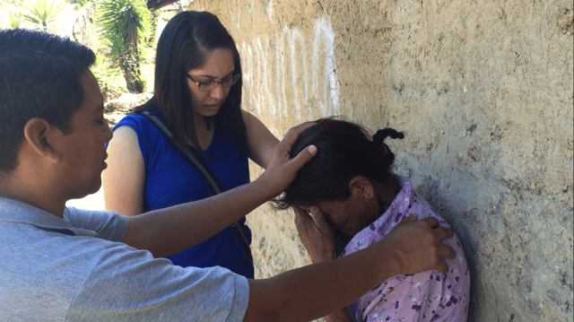 Cardenas prays with a resident in Honduras.