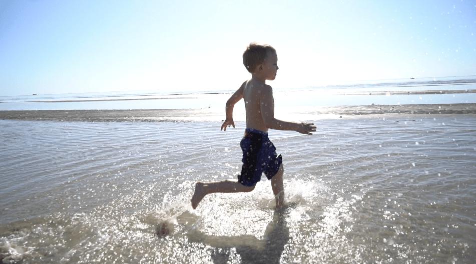 boy running through ocean