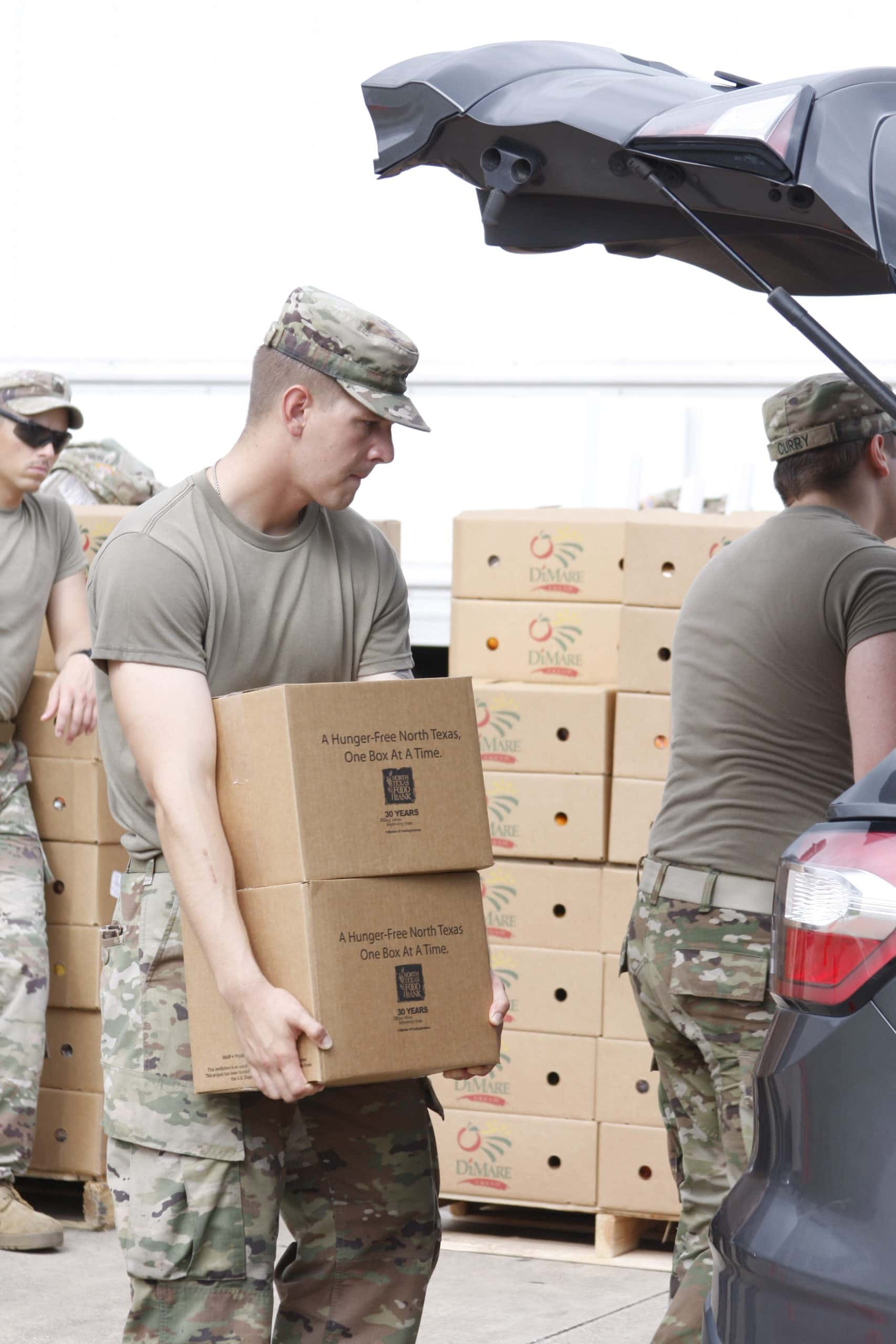 National guardsmen carrying box of food