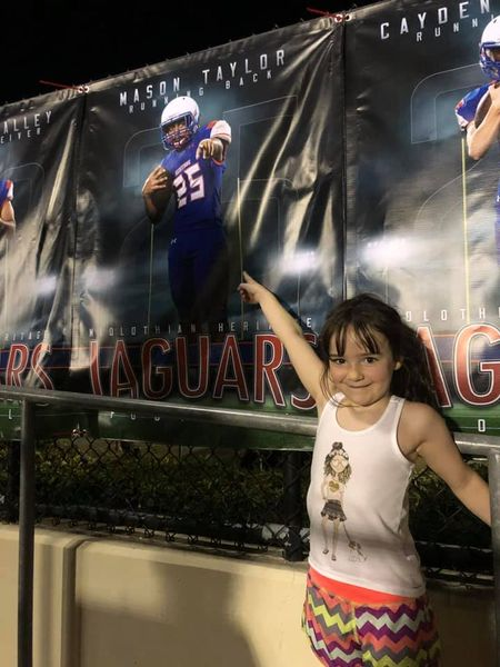 child in front of Heritage football poster