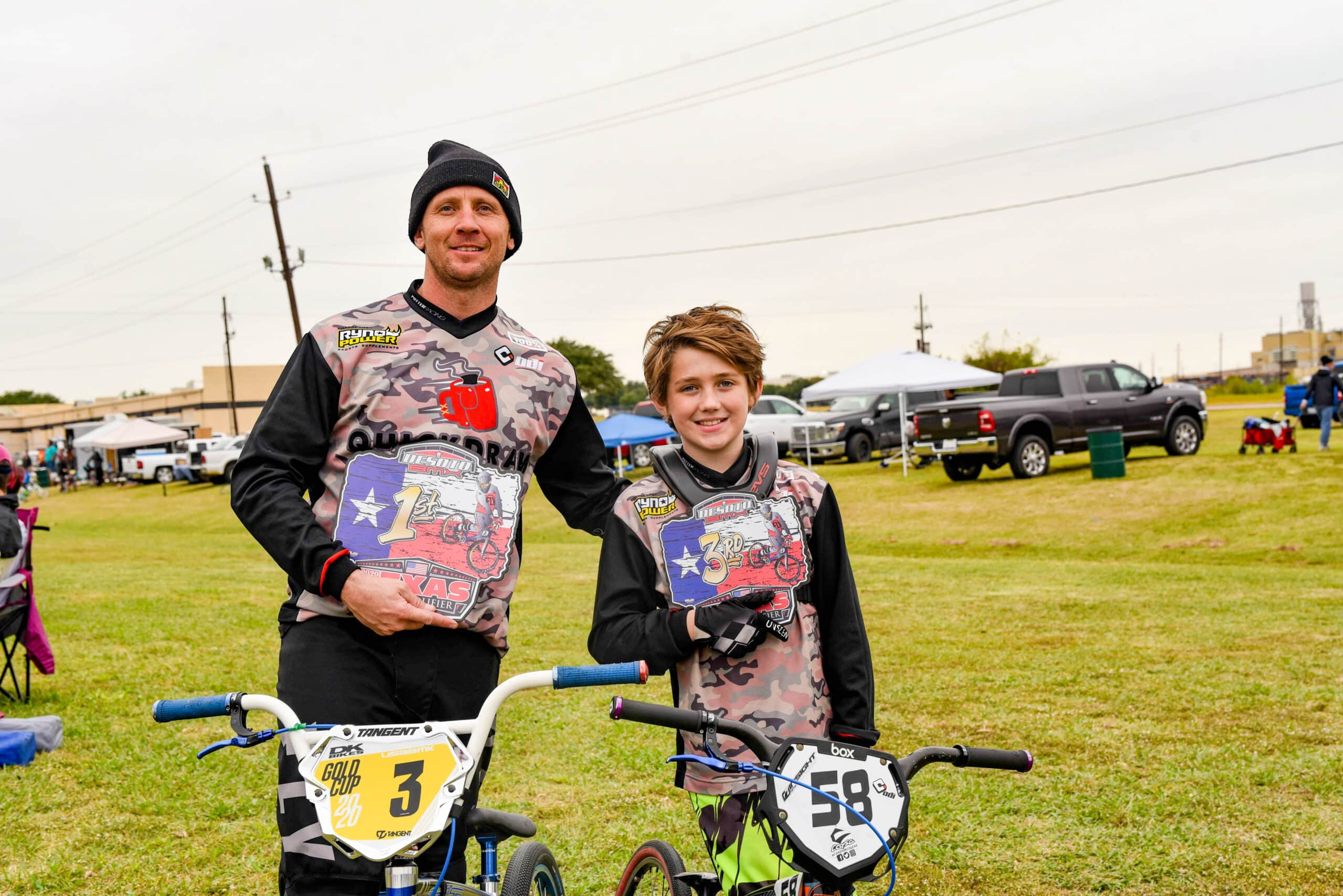 Man and boy showing trophies from BMX race