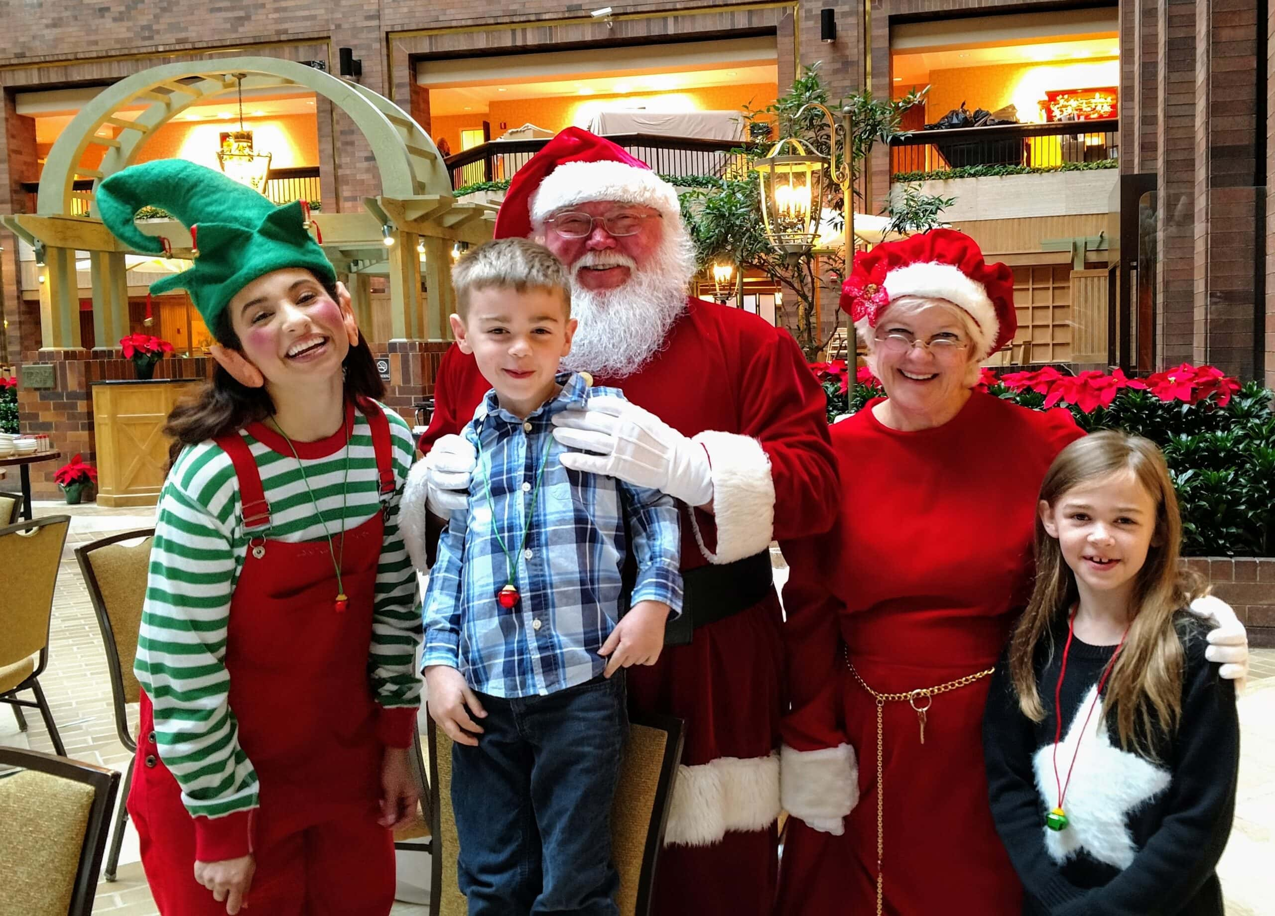 Kids with Santa Mrs Claus and an elf