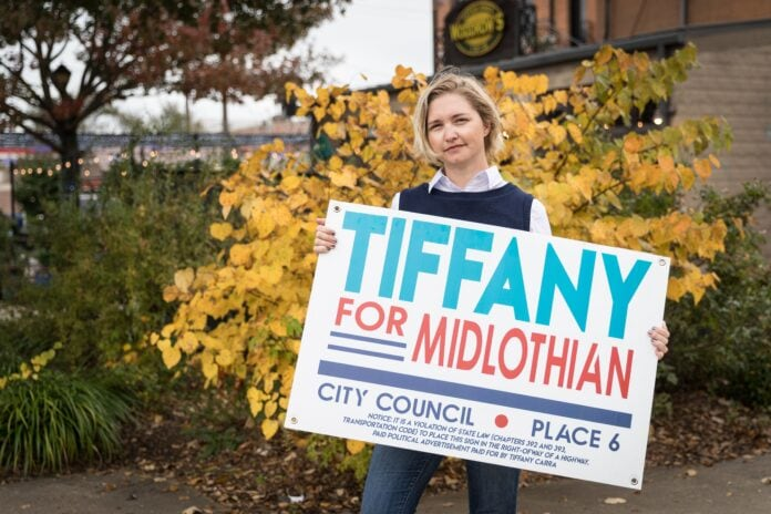 Tiffany Carra holding campaign sign