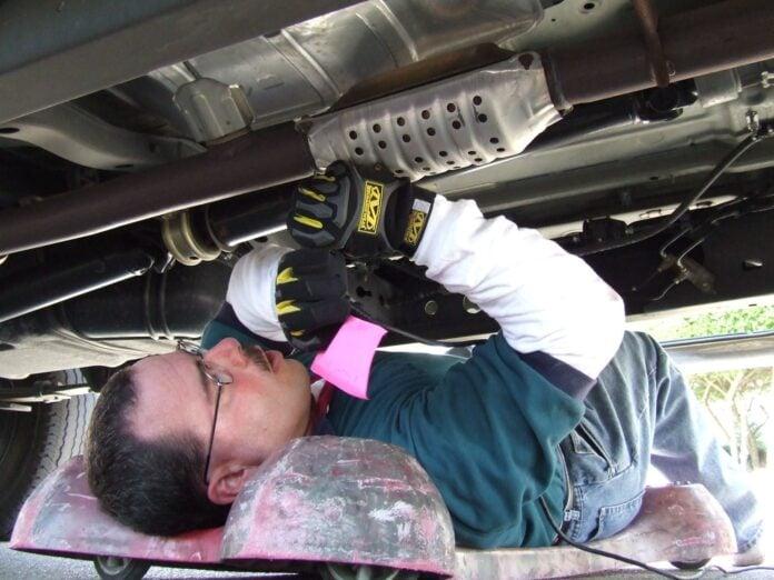 mechanic working on catalytic converter