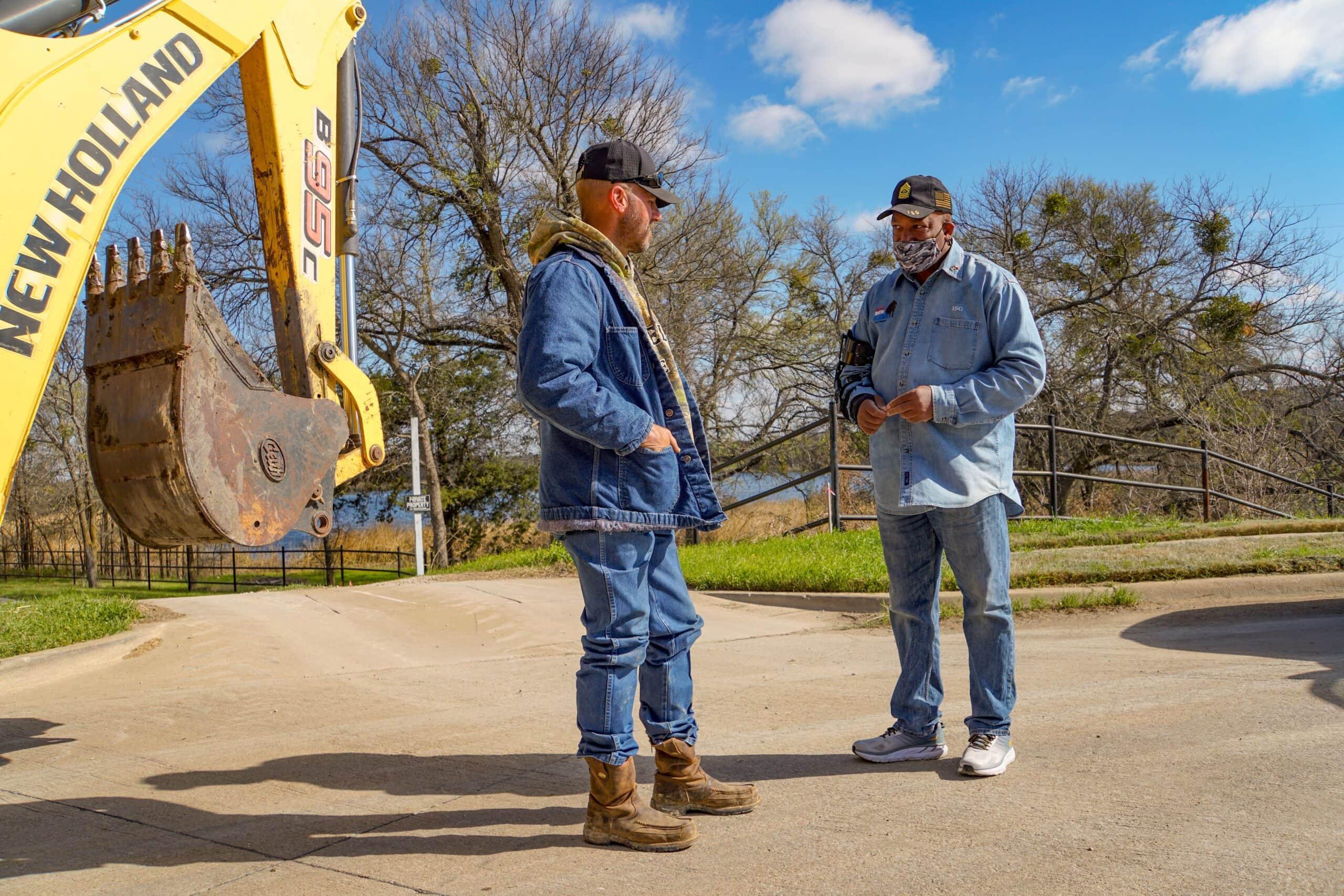 Two men talking by backhoe