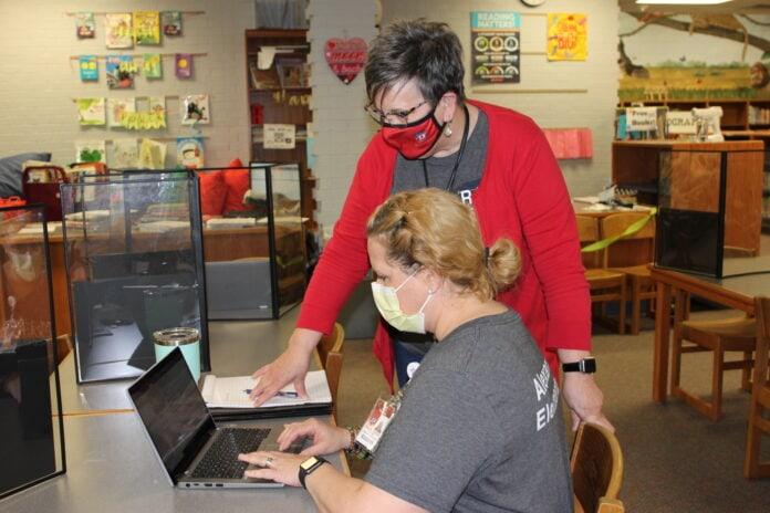 two women use laptop