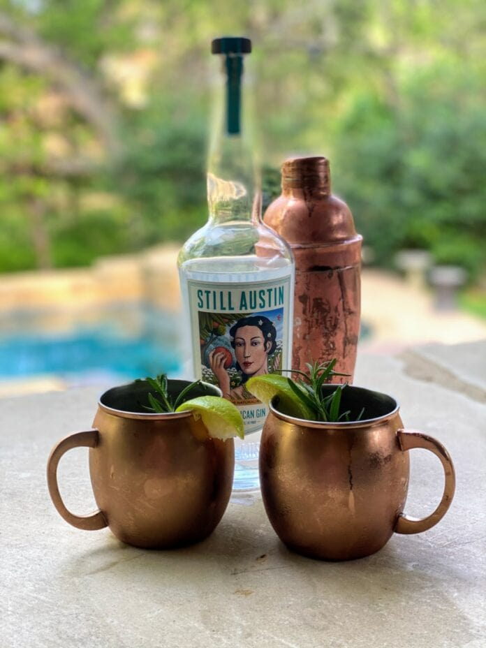 Copper mugs with gin bottle