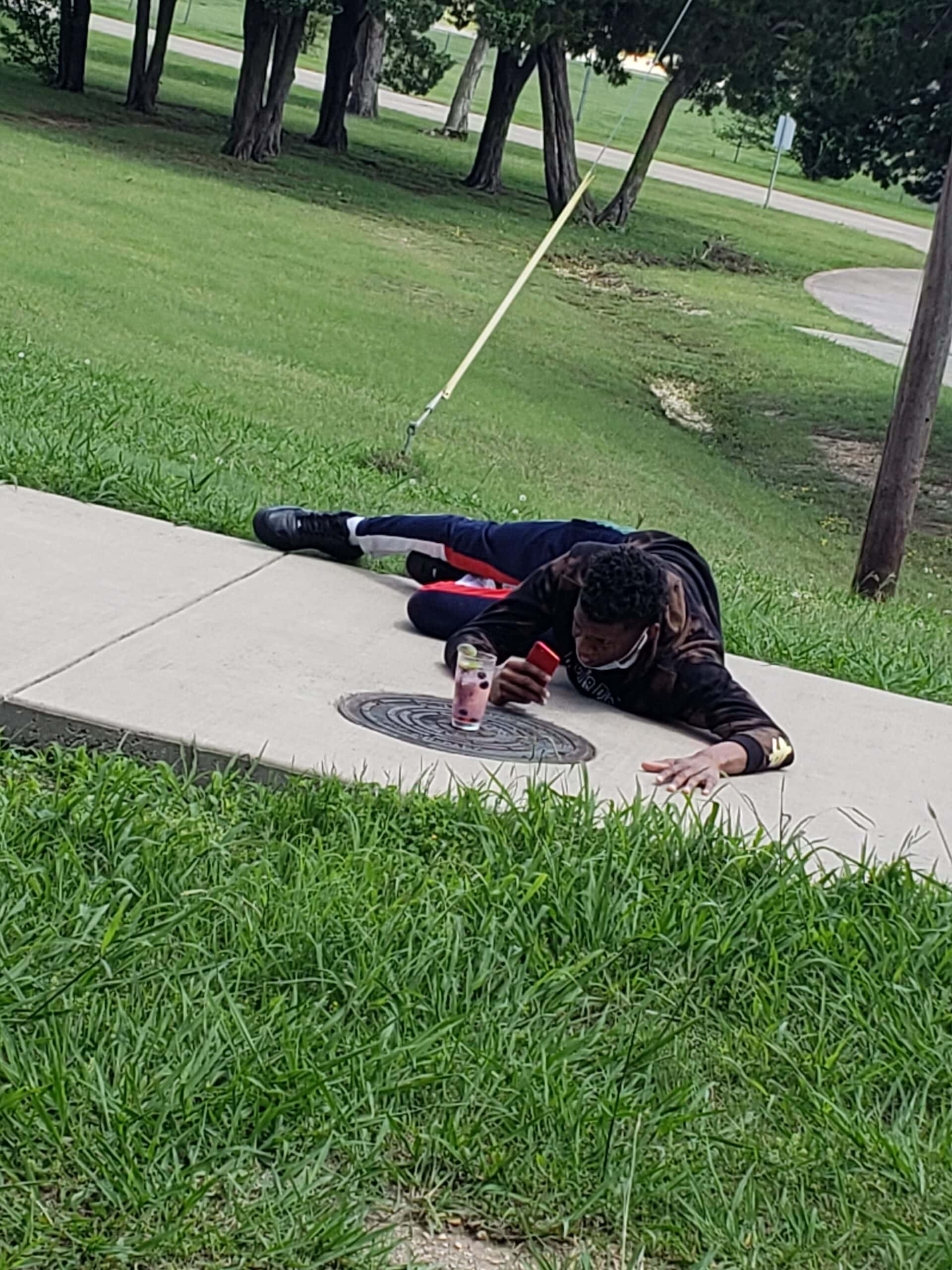 person lying on ground taking photo