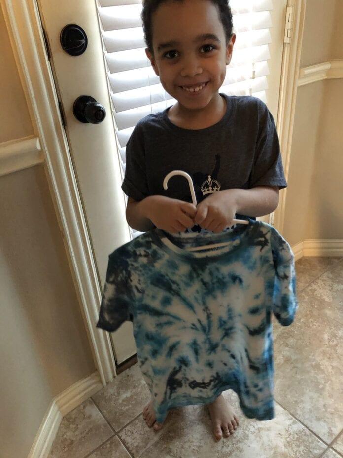 kid holding tye dye tshirt