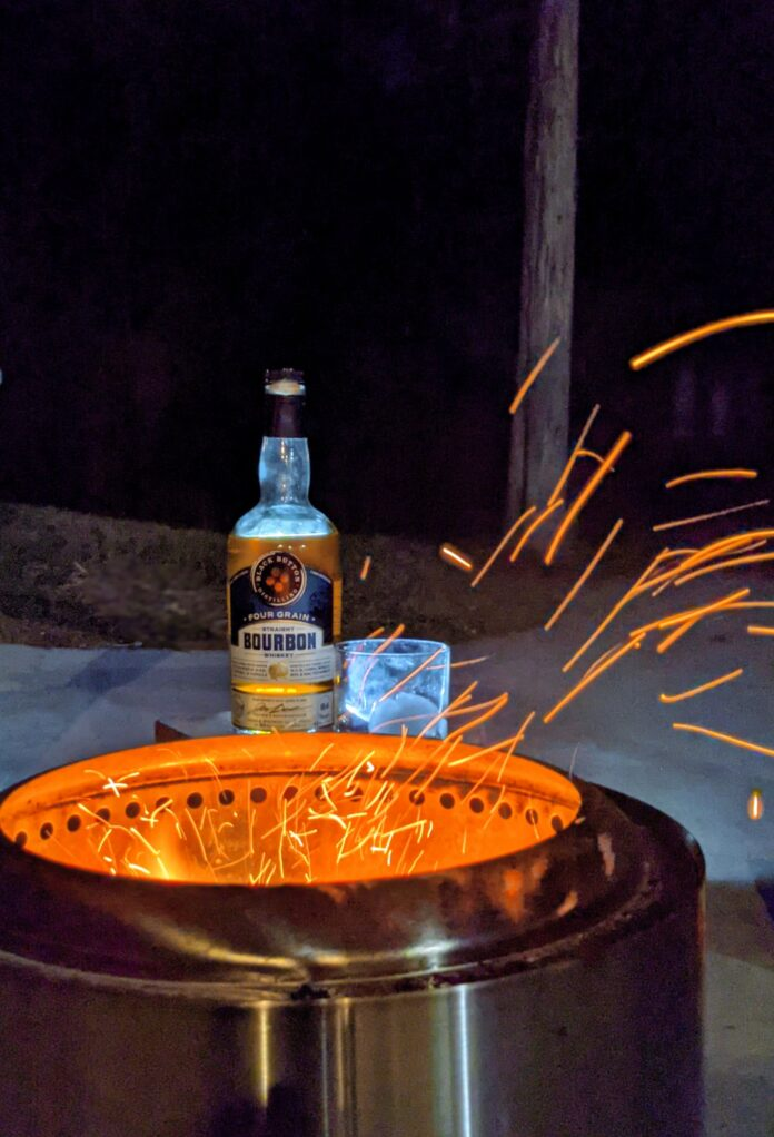 Bottle of black button bourbon by firepit