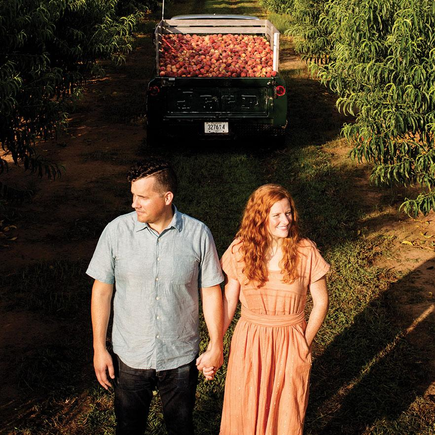 Stephen and jessica Rose stand in peach orchard