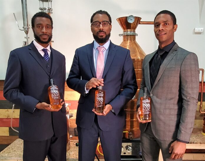 The Brough Brothers holding bottles of bourbon