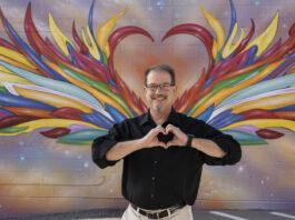 man standing in front of heart mural