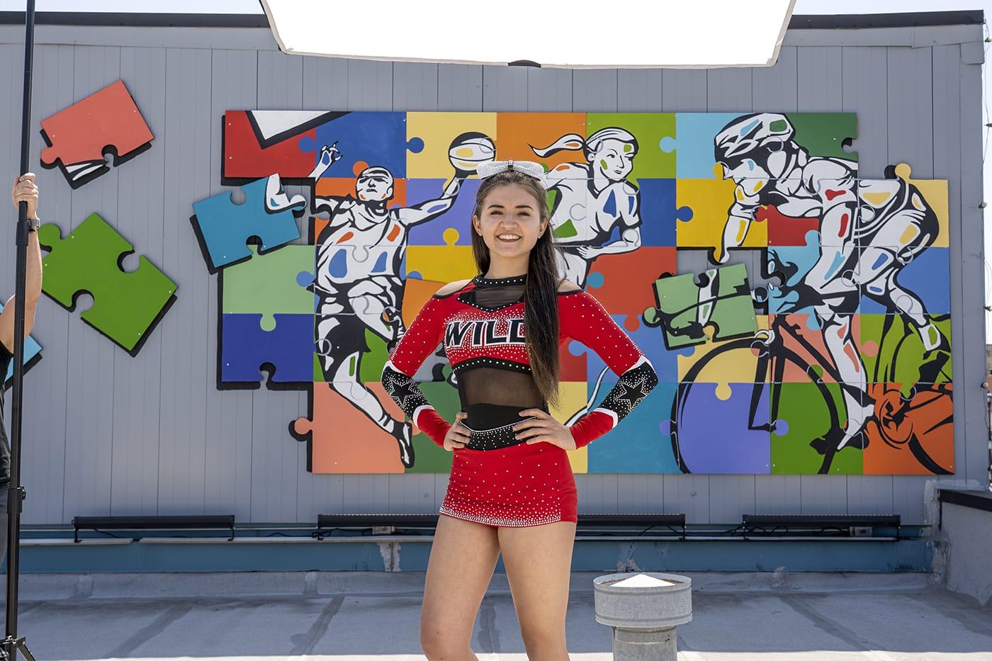 cheerleader in front of bike mural