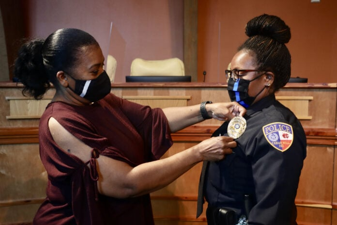 woman placing badge on Officer