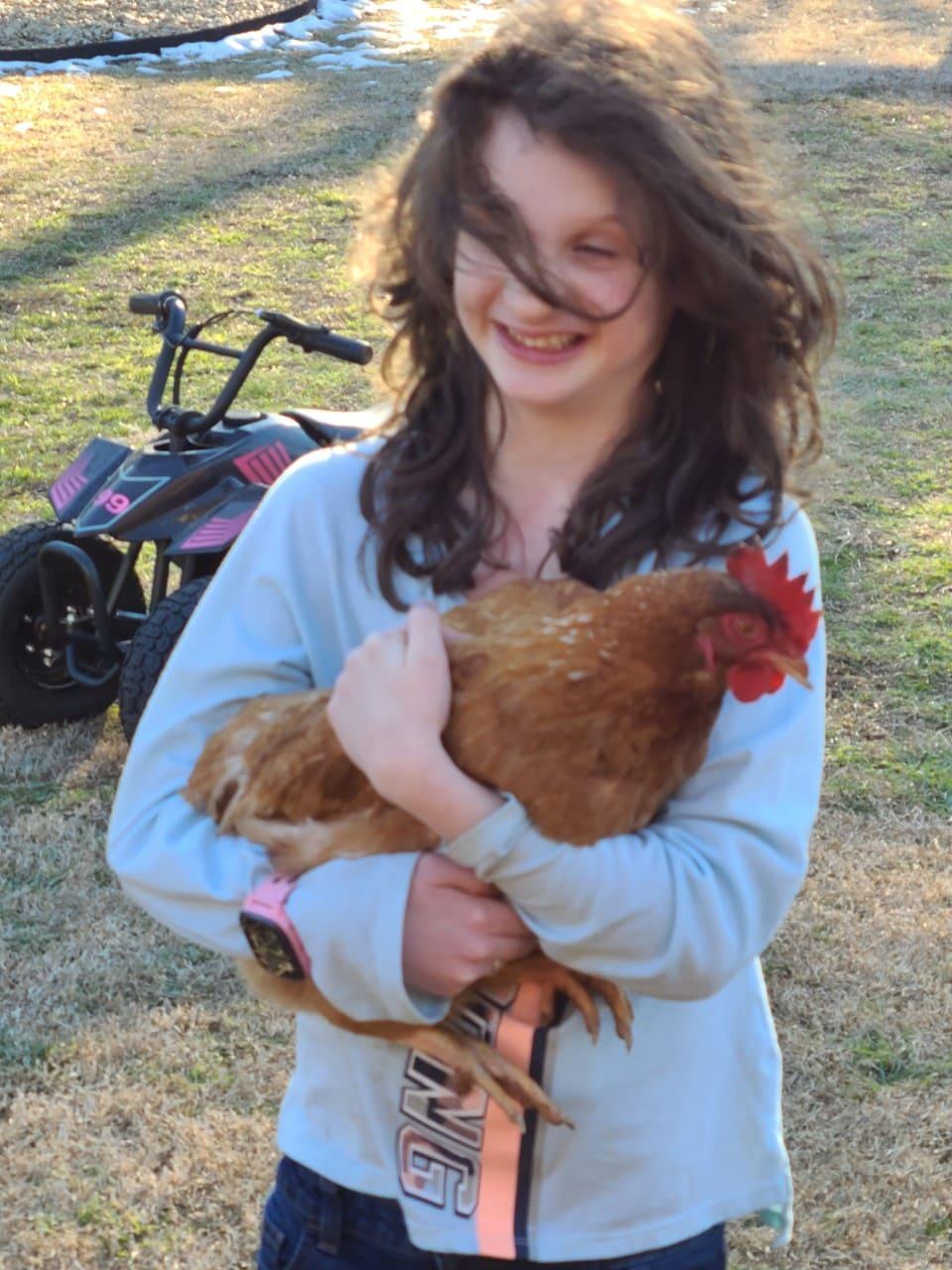 Rachel Derrick holding a rooster