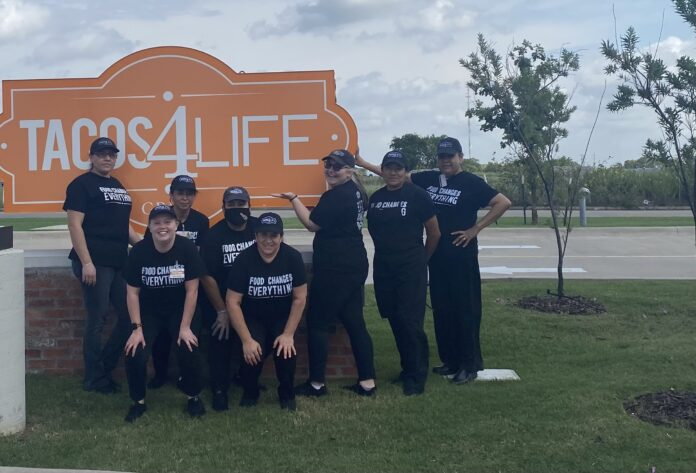Tacos 4 Life staff in front of sign
