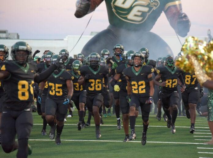 football players run onto field